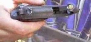 Field strip a Beretta 21A pistol and remove a casing