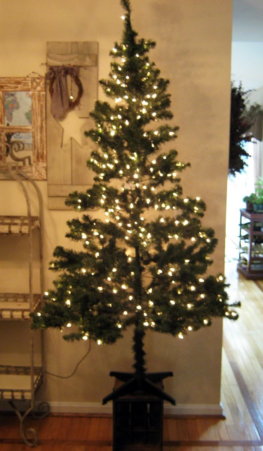 use pine garland to fill in holes - Real Christmas Tree Decorated