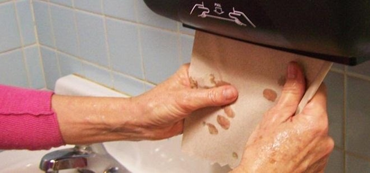 Wet hands pulling a paper towel from a dispenser.