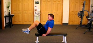 Do a knee curl-up on a bench to achieve six pack abs