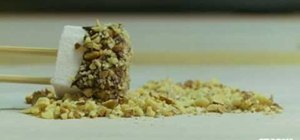 Make a marshmallow pop with chocolate and nuts