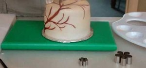 Decorate a miniature cake with painted branches of flowers