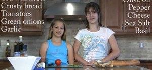 Make feta cheese bruschetta topped with tomato and fresh basil