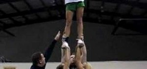 Execute a cheerleading extension with cradle dismount