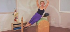 Do a lateral abdominal workout with a Pilates barrel