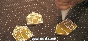 Decorate gingerbread houses with royal icing for Christmas