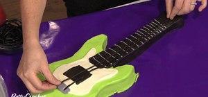 Makean electric guitar shaped birthday cake