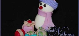 Create a gumpaste snowman with a scarf and hat